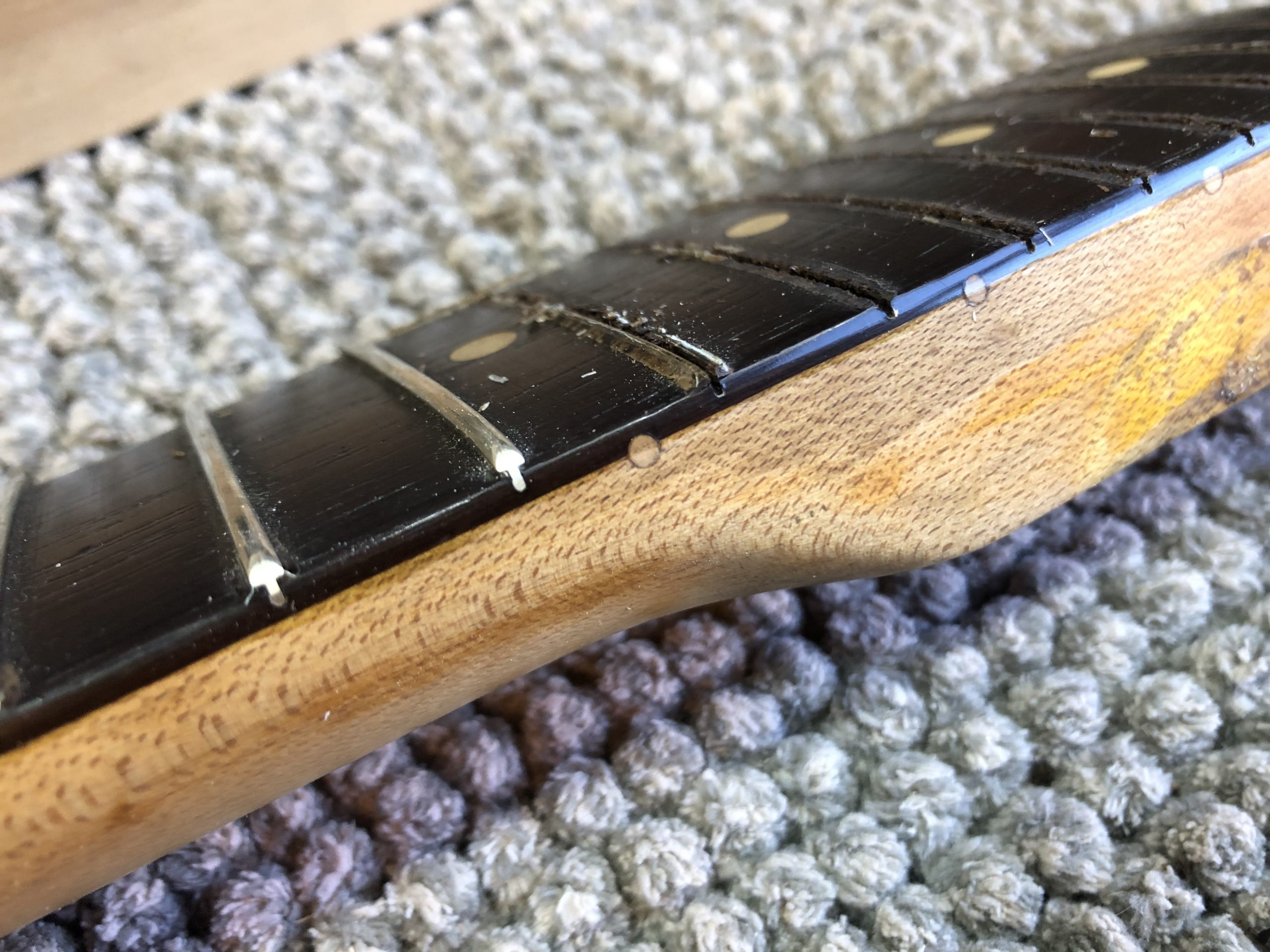 Glue was actually filling the gap where the frets stood proud of the fretboard
